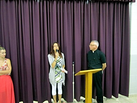 Leah Gordonmakes a presentation to Father Michael on behalf of the Children's Liturgy group