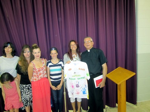 Members of the Children's Liturgy Group present  Father Michael with a specially decorated T shirt