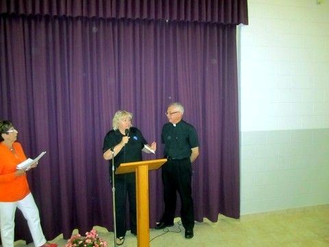 Colleen from the Ozanam Centre presents a gift of thanks to Father Michael for all of his support of  Ozanam Centre