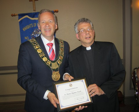 Mayor of St. Catharines, Brian McMullan presents a certificate to Father Michael Basque